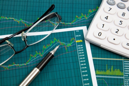 A pen, calculator and spectacles on the Stock chart and financial report photo