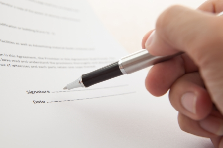 Man hand signing a contract photo