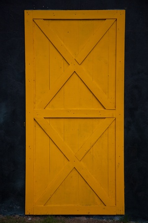 Yellow old wooden door, black wall photo