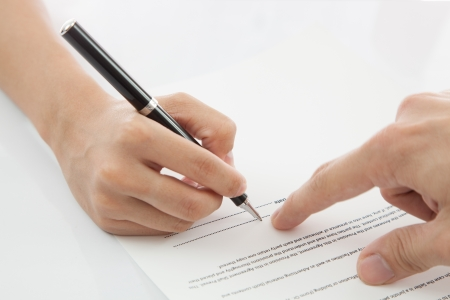 business contract: Female hand signing contract. Stock Photo