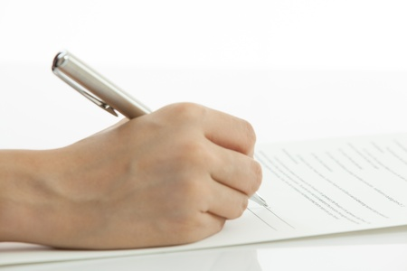 Female hand signing contract on table photo