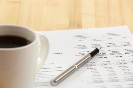 Business report. Cup of coffee on document. photo