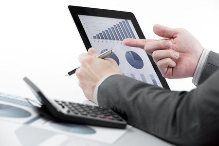 Businessman holding digital tablet with business report photo