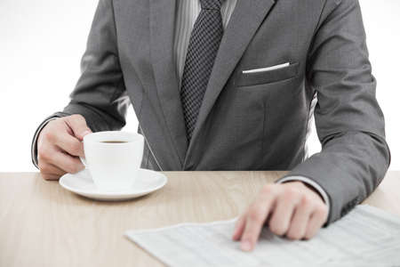 Businessman holding a cup of coffee and reading a newspaper on table photo