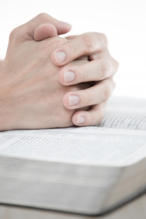 folded hands: hands praying with bible on table Stock Photo