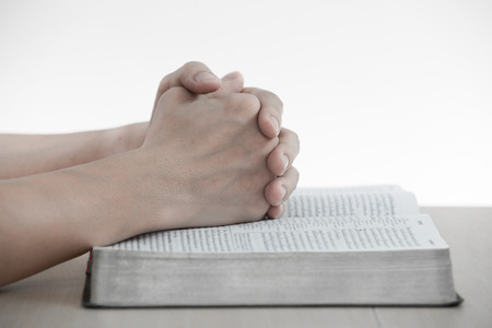 hands praying with bible on table Stock Photo