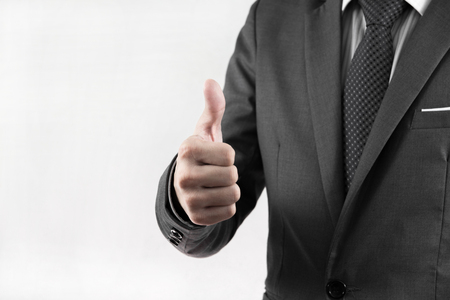 Young business man giving thumb up, isolated on white photo