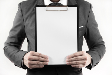 Business man in suit holding a blank clipboard. isolated on white photo