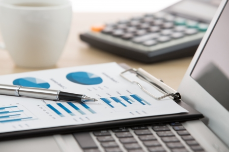 Homme d'affaires analysant graphiques d'investissement avec un ordinateur portable