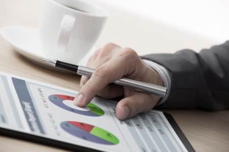 analyzed: graphs and charts analyzed by businessman with coffee