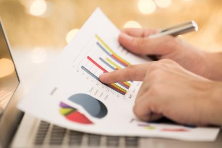 fondos negocios: Negocios que analiza listas de inversión con el ordenador portátil Foto de archivo
