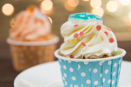 Tasty cupcake with butter cream on lights background
