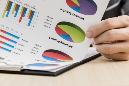 conference call: Businessmans hand showing financial report on table Stock Photo