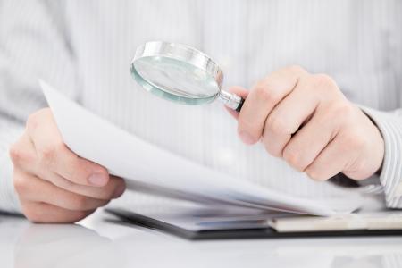 Homme d'affaires regardant à travers une loupe pour les documents