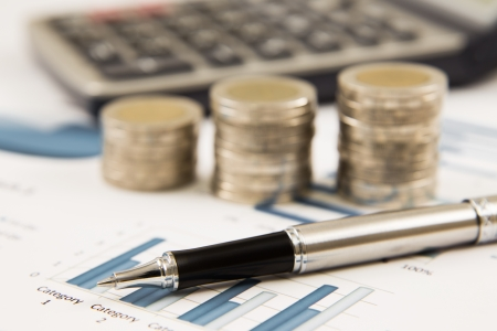 Business diagram on financial report with coins and calculator Stock Photo