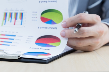 financial gains: Businessmans hand showing financial report on table Stock Photo