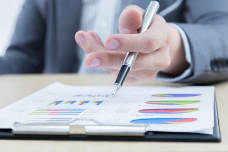 Businessmans hand showing financial report on table Stock Photo