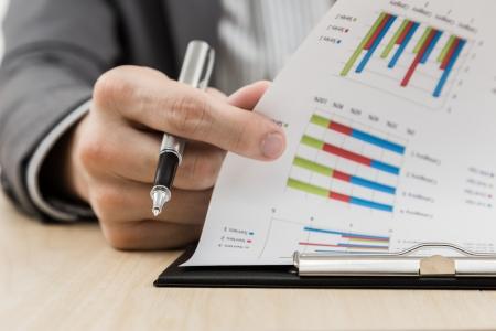 Zakenman hand toont financieel verslag op tafel Stockfoto