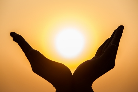 hands holding the sun at dawn photo