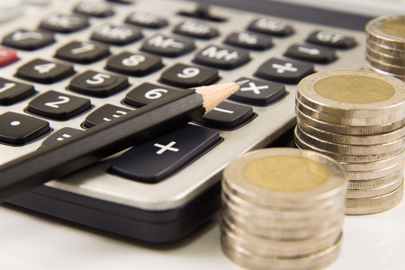 Coins and calculator with pen photo