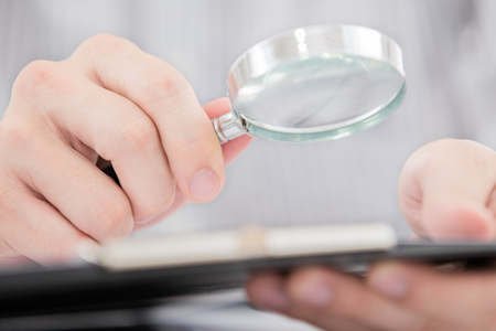 Businessman looking through a magnifying glass to documents photo