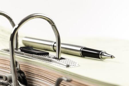 disorganization: office ring binder of document management with a pen