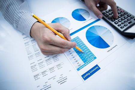 informe comercial: mano del hombre con la pluma y el informe de negocio. Contabilidad