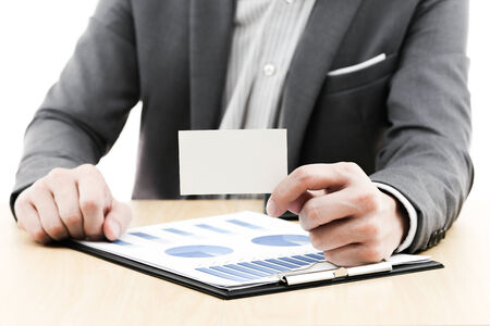 Businessman showing blank business card on table photo