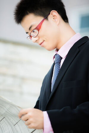 A young businessman reading newspaper outdoors photo