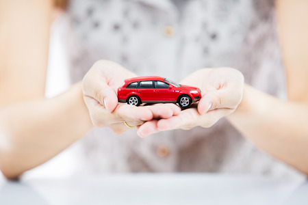 Woman hand with holding red car photo