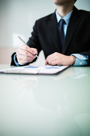 business report and man hand with pen. Accounting photo
