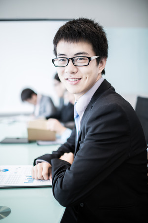 Businessman smiling at the camera while his team is working in the background.Asian photo