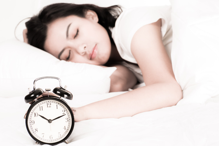 Woman in bed trying to wake up with alarm clock photo