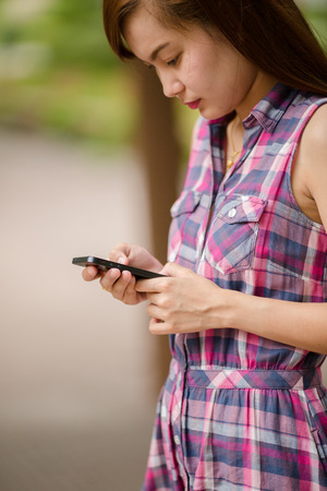 Woman using mobile smart phone in the park. photo