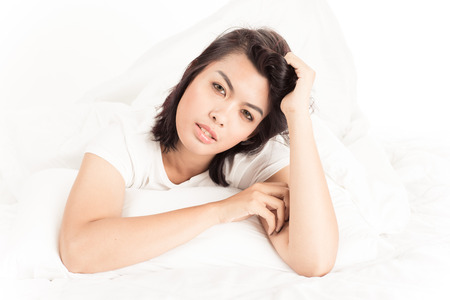 Portrait of a beautiful young woman in bed photo
