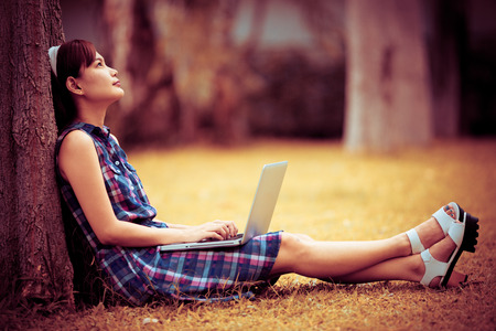 Young Caucasian woman using Laptop on nature photo