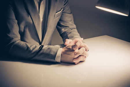 body language: close up of a man in a suit with his hands clasped in front Stock Photo