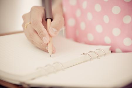 papier lettre: Jeune femme est la r�daction de notes et de la planification de son calendrier Banque d'images