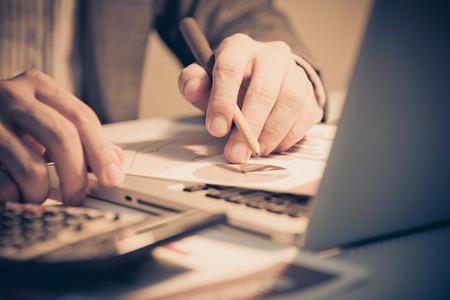contabilidad: Empresario analizar cartas de la inversión con el ordenador portátil. Contabilidad