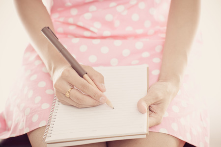person writing: Young female is writing notes and planning her schedule