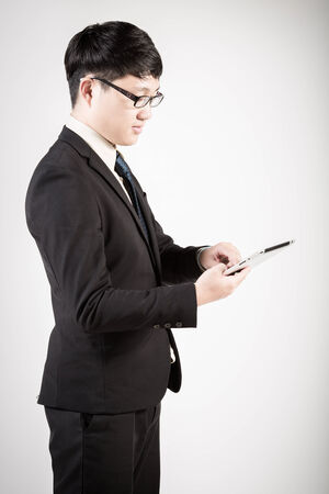 Asian business man using tablet computer isolated on white  photo