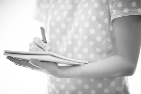 Young female is writing notes and planning her schedule photo