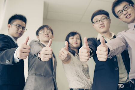 collaborator: Business team holding their thumbs up.Asian