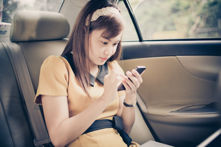 businesswoman with document and laptop in car photo