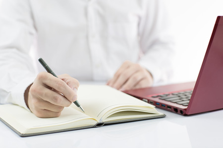 Businessman taking notes with laptop background photo