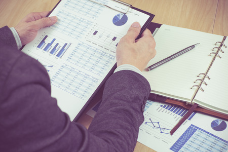 tax forms: man hand with pen and business report. Accounting Stock Photo