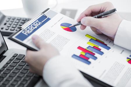 gestion empresarial: Empresario analizar cartas de la inversi�n con el ordenador port�til. Contabilidad