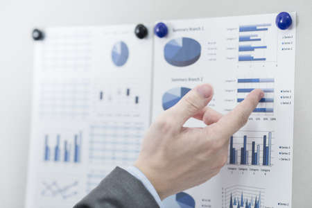 Businessman pointing to flip board with chart in office photo