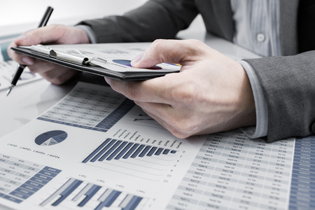 financial performance: Businessman analyzing investment charts. Accounting