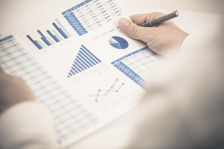 return on investment: Businessman analyzing investment charts with laptop. Accounting Stock Photo